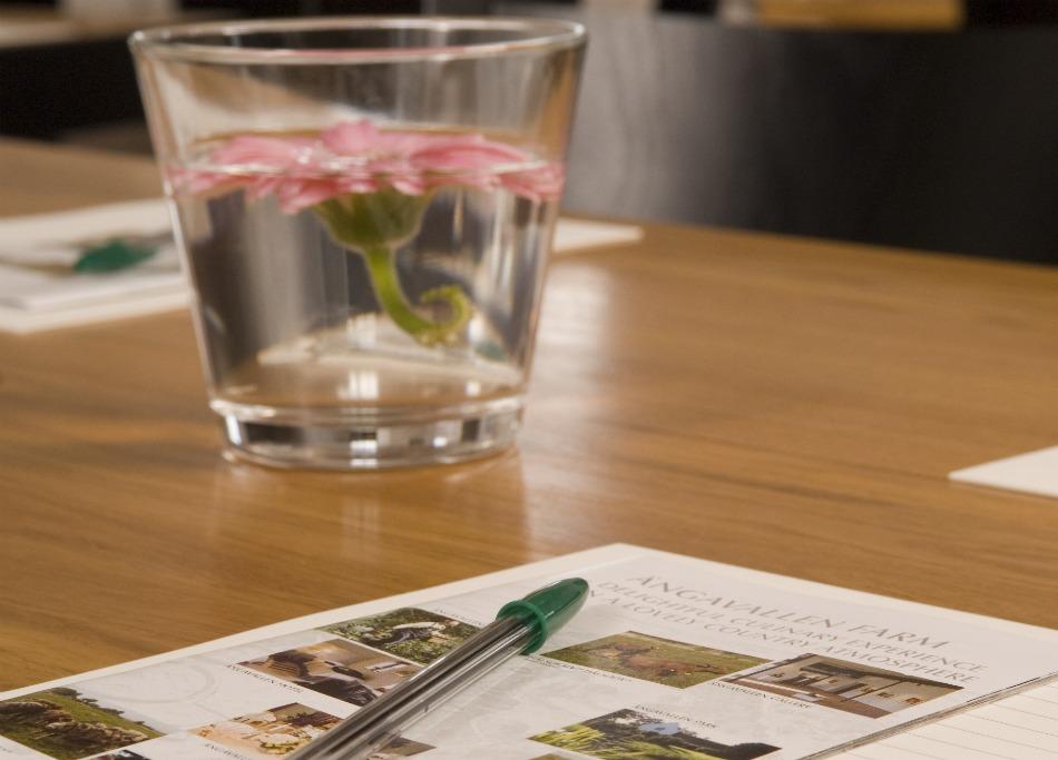 bild på penna, papper och en vas med en rosa blomma i